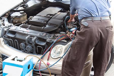 Werktuigkundige met manometer vullen gas in de auto voertuig airconditioning compresser.