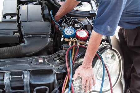 Mechanic with manometer inspecting auto vehicle air-condition compresser with manometer. Banque d'images
