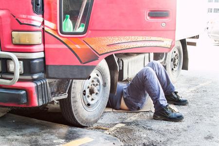 Mechanic onder vrachtwagen repareren vieze vette vette motor met een probleem. Stockfoto