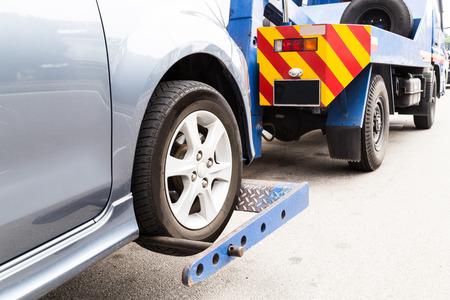 camioneta pick up: Grúa remolca un coche averiado en la calle. Foto de archivo