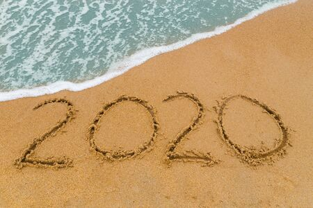 2020 inscription written on sandy beach with wave approaching.