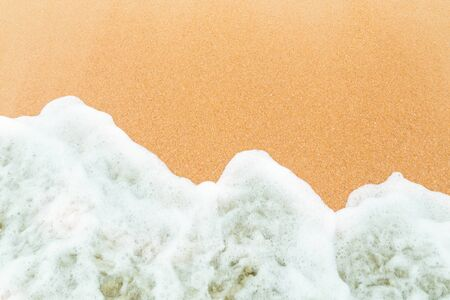 close up: Calm sea waves breaking on sandy beach as background resources.