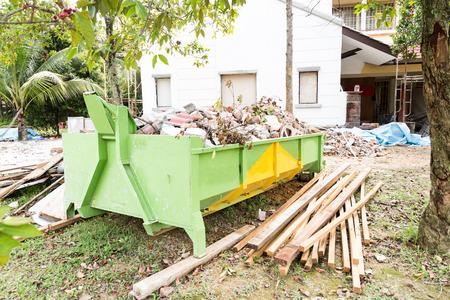 Bouw vuilnisbak met ladingen op bouwplaats, en met onafgewerkte gebouw in de achtergrond Stockfoto