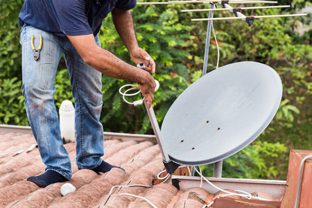 Skillful worker installing satellite dish and television antenna on roof top