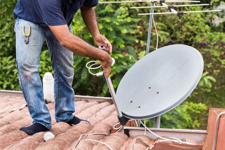 지붕 위에 위성 접시와 텔레비전 안테나를 설치하는 숙련 된 작업자