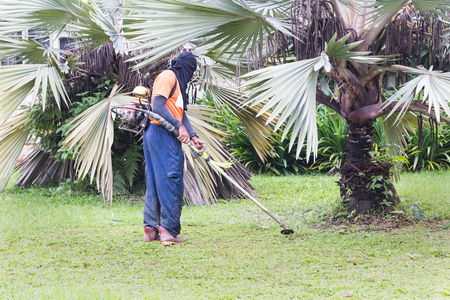 Worker with protective clothing cutting grass with grass cutter machine at residential area