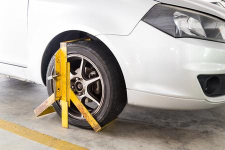 violaci�n: Rueda delantera del coche sujetado por el aparcamiento ilegal, una violaci�n a los aparcamientos comerciales