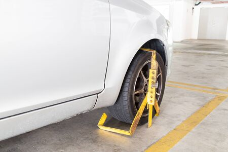 clamped: Front car wheel clamped for illegal parking, a violation at commercial car parks Stock Photo