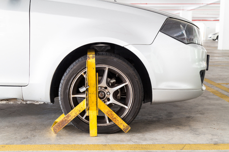 violaci�n: Front car wheel clamped for illegal parking, a violation at commercial car parks Foto de archivo