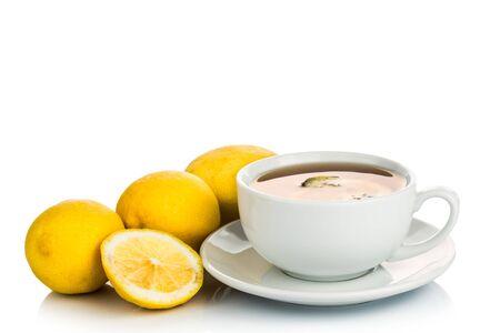 stimulating: Refreshing hot tea with lemon slice and lemon fruits on white backlit background Stock Photo