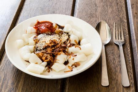 Servire del delizioso Cheang Cheong di Penang con le salse, il sesamo e la scalogna fritta sul tavolo di legno Archivio Fotografico - 48617915