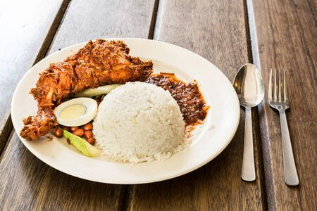 lemak: Delicious and aromatic Nasi Lemak with fried chicken served on wooden table, a popular Malaysian delicacy