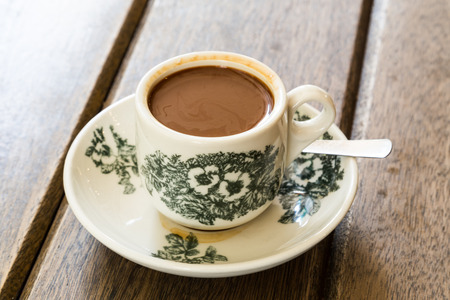 Traditionele oosterse Chinese koffie in vintage mok en schotel op houten tafel in soft focus instelling met omgevingslicht Stockfoto