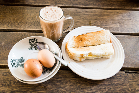 Common oriental breakfast set in Malaysia consisting of teh tarik, toast bread and half-boiled egg