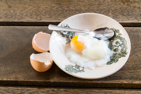 Asian Chinese half soft boiled egg served on old fashioned Oriental saucer