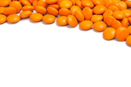 chocolate candy: Top right frame of orange color chocolate coated candy on white background with space for text