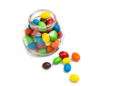 Transparent glass jar with colorful chocolate coated candies on white background