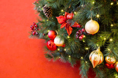 christmas backdrop: Decorated Christmas fir tree with sparkling lights on red backdrop
