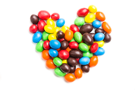 mm: Heart shape formed using colorful milk chocolate candies with crisp shell on white background Stock Photo