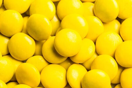 thin shell: Close up on pile of delicious yellow milk chocolate candies with thin crisp shell