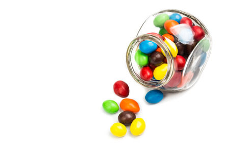 mm: Transparent glass jar with colorful chocolate coated candies on white background