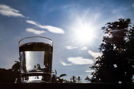 agua purificada: Silueta de agua purificada refrescante en vidrio transparente contra el cielo azul, las zonas verdes y los rayos del sol