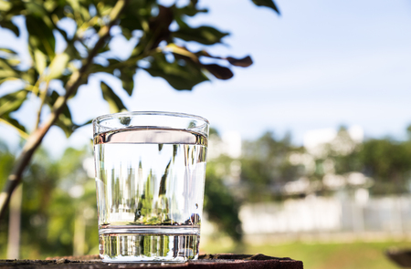 purified: Refreshing purified water in transparent glass against blue sky, cloud and greeneries