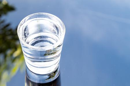 acqua bicchiere: Rinfrescante acqua purificata in vetro trasparente con la riflessione contro il cielo blu, nube e greeneries Archivio Fotografico