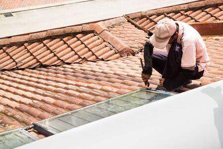 Werknemer vaststelling van zonneboiler op de top van het dak tijdens onderhoudswerkzaamheden