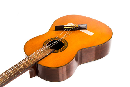 guitars: Broken brown classical guitar with detached bridge from body isolated in white background Stock Photo