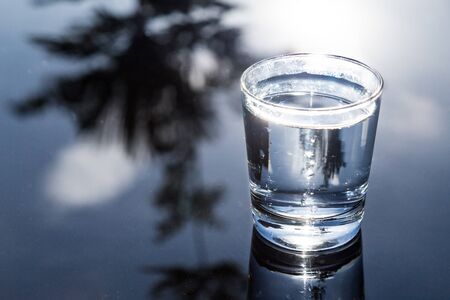 purified: Refreshing purified water in transparent glass with reflection against blue sky, cloud and greeneries