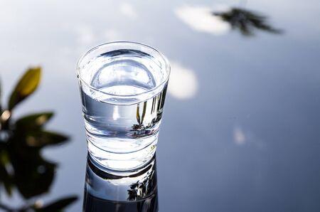 agua purificada: agua purificada refrescante en vidrio transparente con la reflexión contra el cielo azul, las nubes y zonas verdes