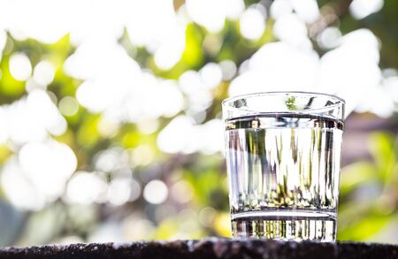 agua purificada: agua purificada refrescante en vidrio transparente contra el fondo con zonas verdes