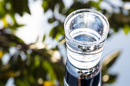Refreshing purified water in transparent glass with reflection against blue sky, cloud and greeneries Stock Photo