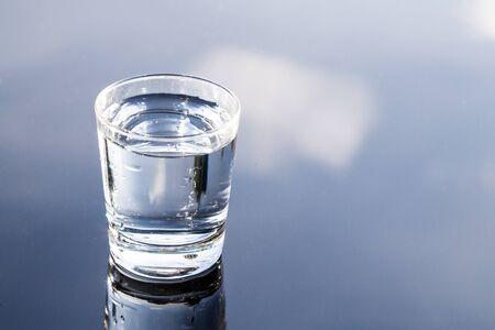 agua purificada: agua purificada refrescante en vidrio transparente con la reflexión contra el cielo azul y la nube