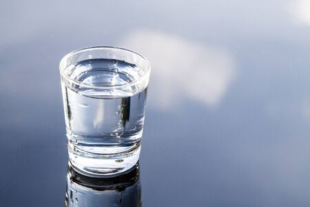 purified water: Refreshing purified water in transparent glass with reflection against blue sky and cloud Stock Photo