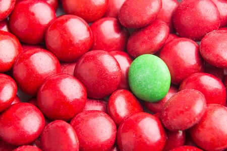 heaps: Concept of selective focus on green chocolate candy against heaps of red candies in background