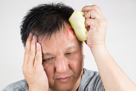 Closeup on man treating his injured painful swollen forehead bump from accidental fall  with icepack