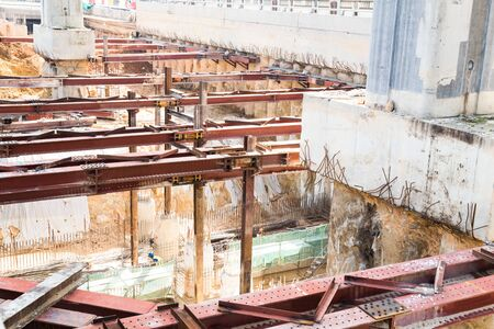 site: Closeup on construction of tunnel underpass underway with metal beams and huge pillar beneath train line