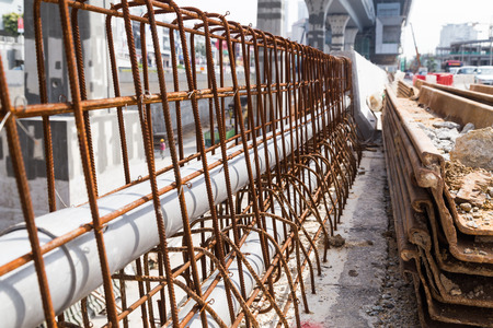 concrete construction: PVC pipes lined within rebar of concrete divider in road construction site