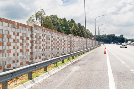 insulate: Concrete noise barrier wall along busy noisy highway insulate surrounding residential area