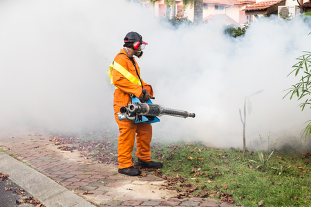 disease control: Worker fogging residential area with insecticides to kill aedes mosquito breeding ground, carrier of dengue virus