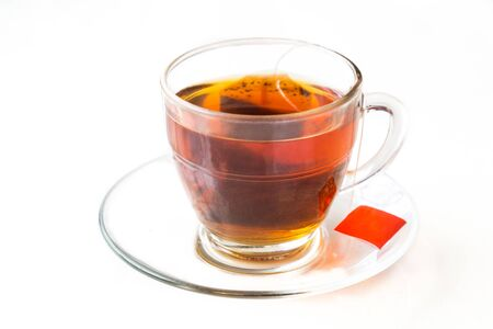 ambient light: Hot aromatic tea with tea bag in transparent cup and saucer on ambient light Stock Photo