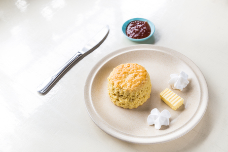 scones: Simple and delicious English scones set with butter, cream and strawberry jam with ambient light Stock Photo