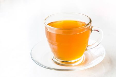 glass cup: Hot aromatic honey tea in transparent cup and saucer with ambient light Stock Photo