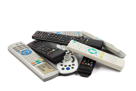 Stack of modern audio video remote wireless control device in white background