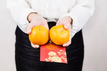 mandarin oranges: Perspective view of woman giving mandarin oranges and red envelop with Good Luck character, a tradition during Chinese New Year celebration