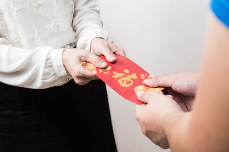 red hand: Woman giving red envelop containing money, with Good Luck character, a tradition during Chinese New Year celebration