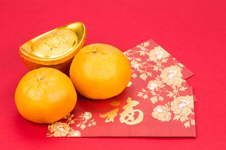 chinese people: Mandarin oranges with decorative gold nugget, and red packets with Good Luck character in Chinese on red background
