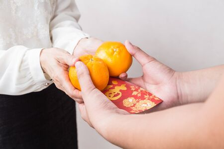 women: Woman giving mandarin oranges and red envelop with Good Luck character, a tradition during Chinese New Year